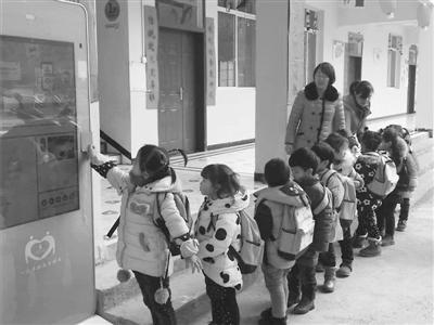 幼儿园小朋友放学时正在排队刷卡