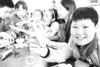 指导小学生制作,放飞飞机模型.