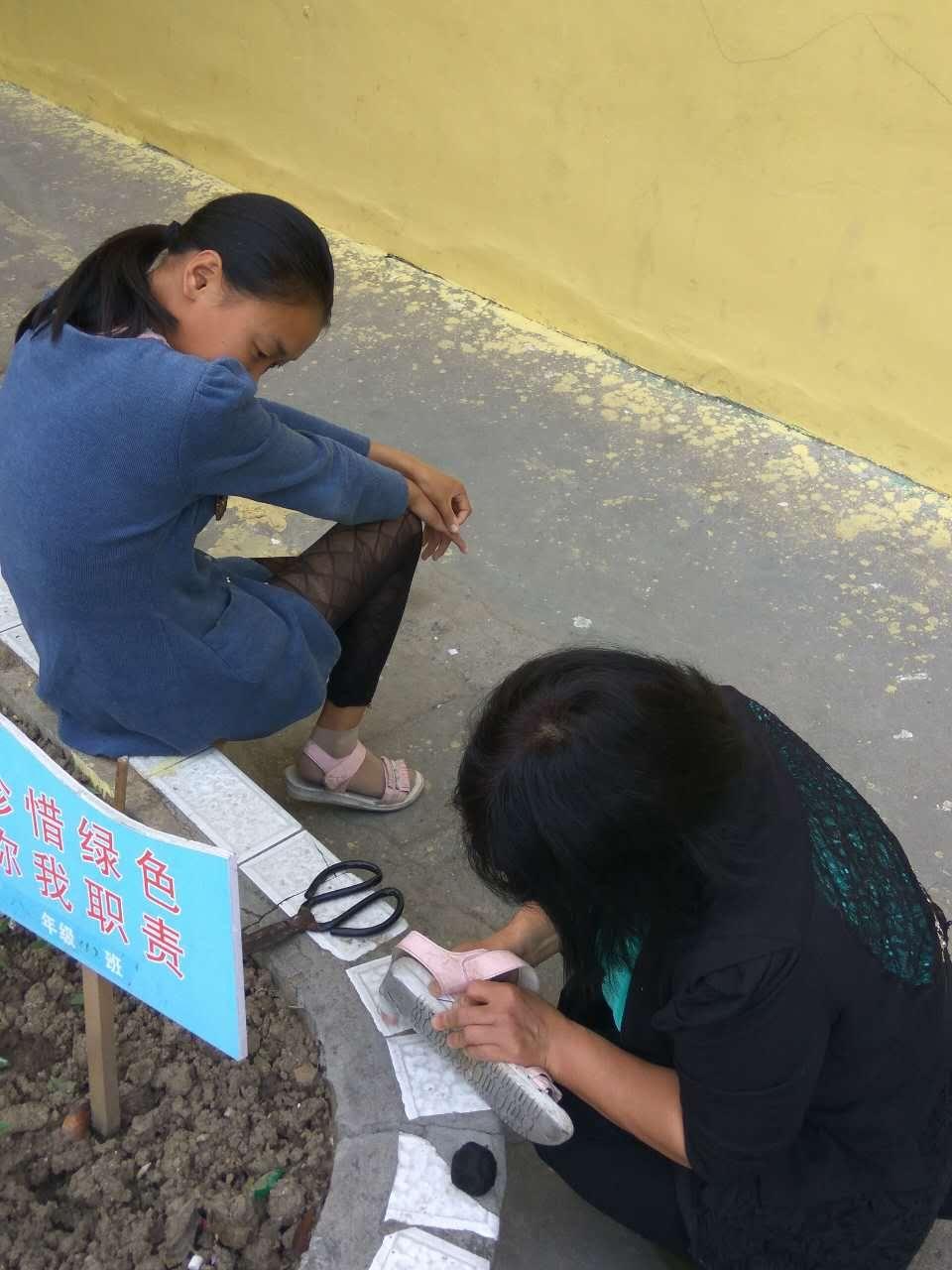 老师为留守儿补鞋 女孩偷偷抹泪