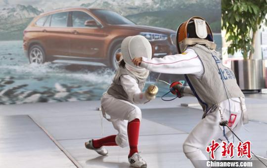 比赛中 主办方   中新网北京6月3日电 (记者 王婧)儿童击剑挑战赛(花剑)3日在北京宝诚百旺展厅举行,面向8到10岁的少年儿童。家长普遍认为,击剑运动对训练儿童反应速度、灵活度有帮助。   本次活动由达毅思创、盈动体育、凯旋击剑训练中心、北京和睦家卫星诊所联合主办,北京宝诚宝马承办。为了推广击剑项目,活动设置了比赛、击剑体验、亲子游戏、运动防护知识普及等环节。  教练教授击剑基本动作 王婧 摄   场地一角,凯旋击剑训练中心的叶教练正在教一位小女孩基本的击剑动作。跟我一起,手臂向前伸把剑刺出去,刺到