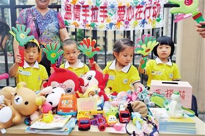 活动现场,两江实验幼儿园的小朋友们将自己的玩具,书籍,以及和爸爸