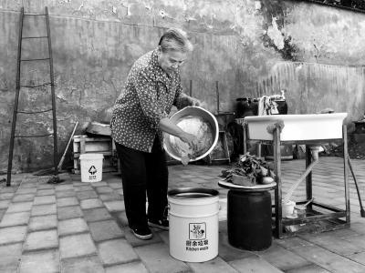 将废弃菜叶倒进厨余垃圾桶,这对高永珍老人已是再平常不过的事.