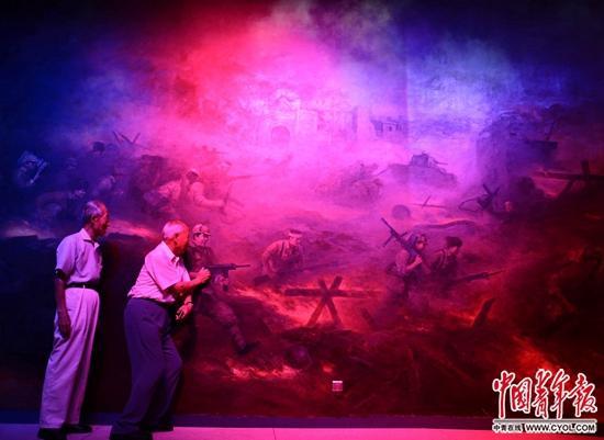 7月22日,北京,中国人民革命军事博物馆,一位老者在攻克锦州景观前触摸投影墙上的战士。铭记光辉历史 开创强军伟业庆祝中国人民解放军建军90周年主题展览27日起正式对公众开放。中国青年报中青在线记者 陈剑/摄   本报北京7月23日电(中国青年报中青在线记者 苗晓雨)朱德在南昌起义时使用的手枪、曾跟随支前民工参加过淮海战役的手推车、五五式元帅礼服和勋章、雷锋日记、汶川地震抢险救灾战士写在挎包上的遗书、辽宁号航空母舰赴南海海域执行训练任务时的照片这些平日里难得一见的珍贵文物和文献资