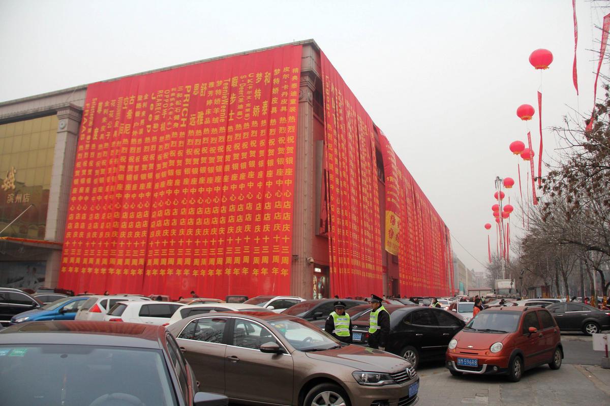 山东滨州一商场举行开业庆典活动,遮天蔽日的条幅挂满了商场大楼,气球