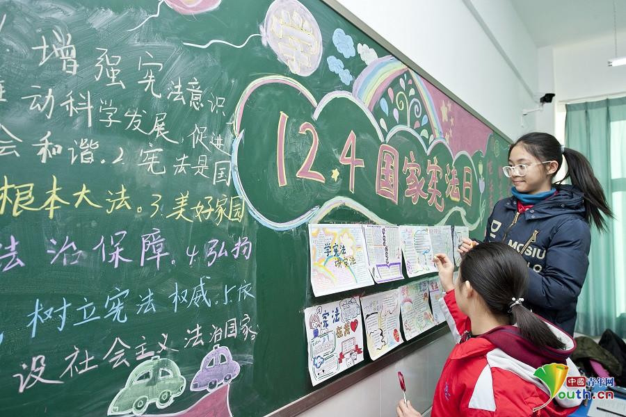 学学生正在绘制宪法宣传主题黑板报.  摄-秦皇岛开发区各学校开展
