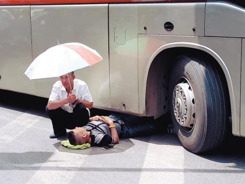 男子过马路时玩手机 被客车卷进轮下脚踝骨折(图)