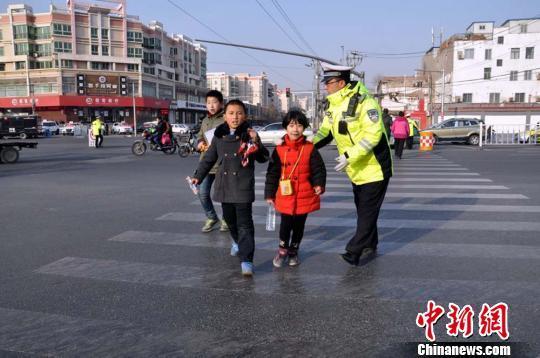 图为兰州交警带领孩童通过马路。   魏立武 摄
