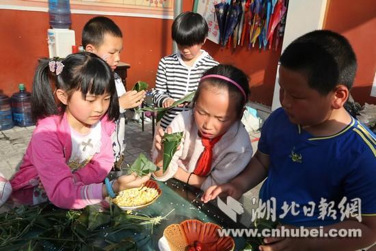 鹤峰爱心志愿者陪留守儿童包粽子庆端午(图)