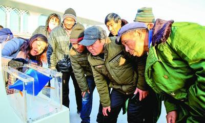 """宁夏回族自治区文化科技卫生""""三下乡""""集中示范活动中,来自科技部门的工作人员(左一)在为群众讲解""""锥体上滚""""的操作。新华社发"""