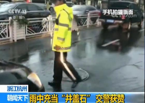 """杭州交警雨中充当""""井盖石"""" 确保过往车辆安全"""