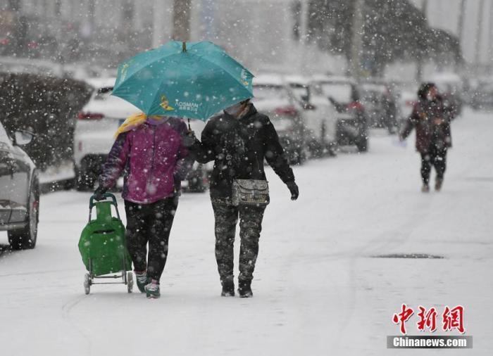 11月13日,長春市民在街頭冒雪出行。 張瑤 攝