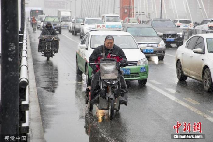 11月13日,吉林迎來入冬以來的首場降雪,市民冒雪出行。圖片來源:視覺中國
