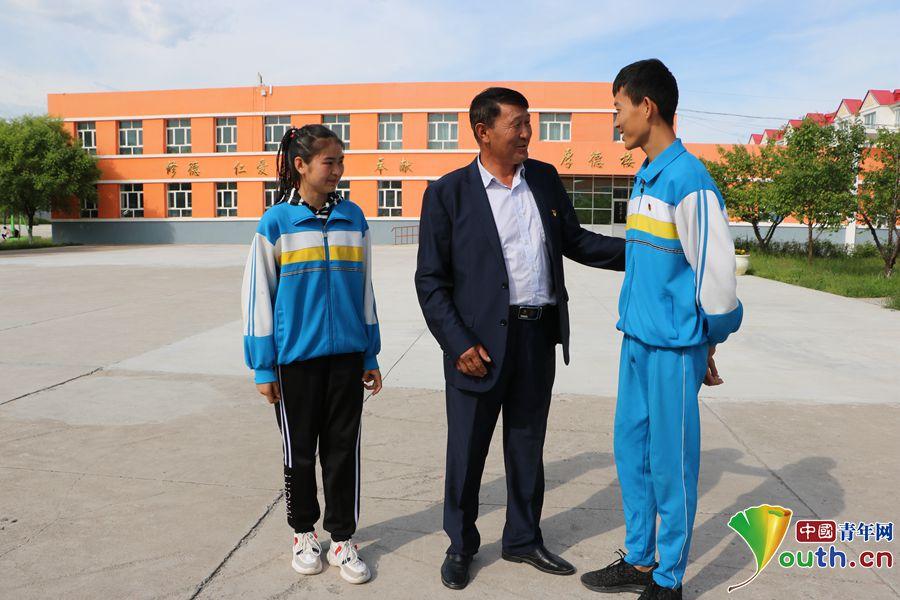 努尔江与受资助学生巴哈提努(左)、王振江(右)在一起亲切交谈。中国青年网记者 李川 摄