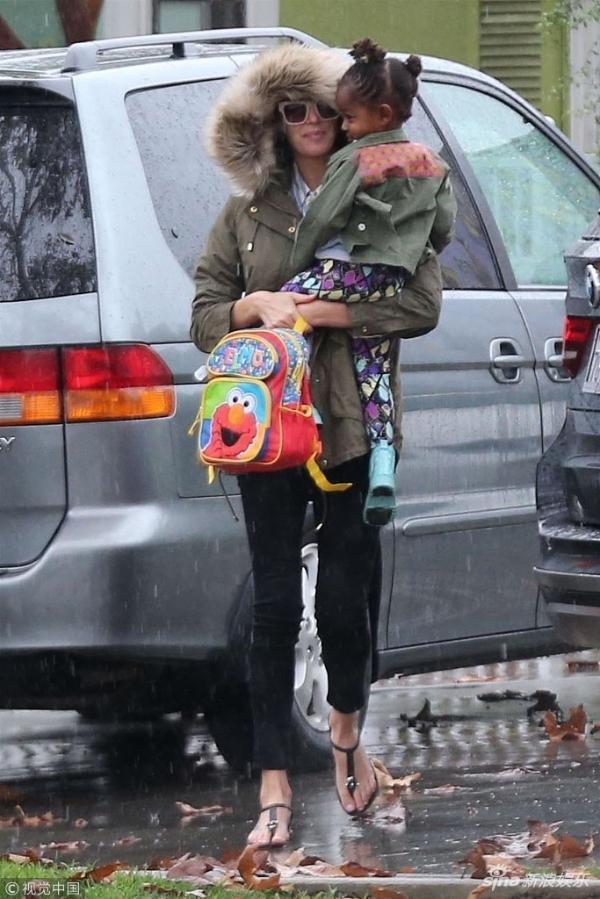 组图:塞隆雨天抱女儿出街 上棉袄下凉鞋纤细长腿吸睛